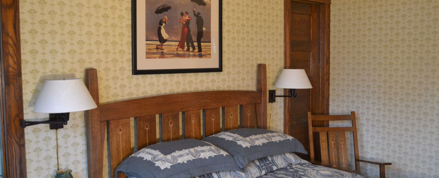 Ghirardelli suite bedroom with Stickley quarter sawn oak bed with Arts and Crafts design bedding, end tables and rocker.
