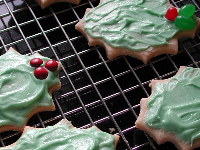 Beautifully decorated holly shaped christmas cookies with green icing and red candies and berries on a grid patterned cooking rack.
